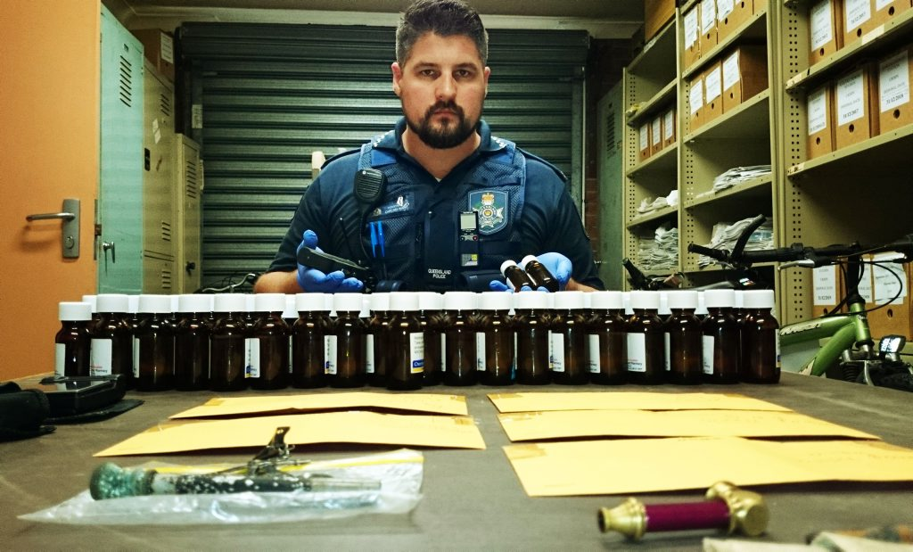 DRUG HAUL: Constable Carl Newman with 191 vials of methadone, a knuckle-duster/taser and drug paraphernalia that were seized in the raid.
