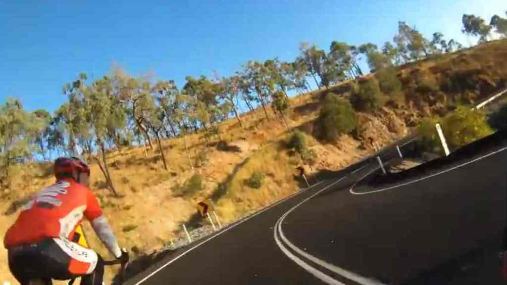 Still of video of cyclist overtaking others over double white lines going down Mt Morgan Range