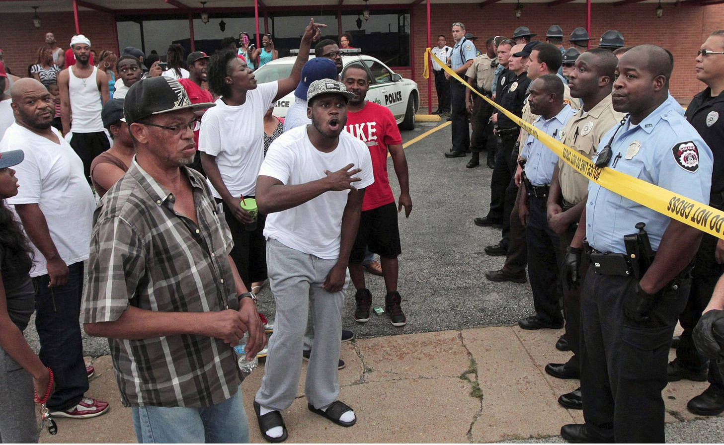 Ferguson police officers try to calm down a crowd near the scene where 18-year-old Michael Brown was fatally shot by police