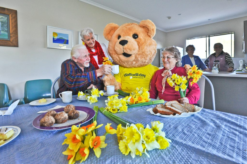 Dougal Bear gave Daffodils to Shearwater Lodge patient Steve Langley and Anne Hillier and Derlein Pennell whose husbands are patients in the facility, while enjoying a friendly chat over a cup of tea and cake. Photo: Rob Wright / The Coffs Coast Advocate