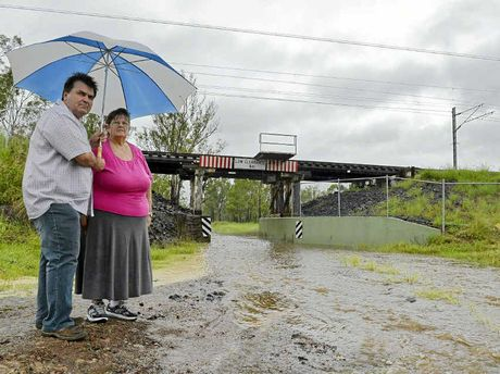 FLOOD FEARS: Thagoona flood victim Janelle Brazier and Councillor David Pahlke stand next to pooling rainwater near a rail bridge off Adelong Ave. Janelle has twice experienced metre-high floodwaters through her property in the past four years.
