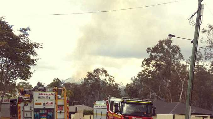 FIRE FEARS: Dark smoke billows over houses.