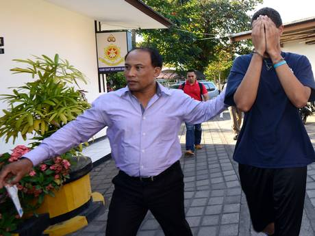 A police officer escorts suspect Tommy Schaffer, 21, during an investigation at a police office in Nusa Dua on Indonesian resort island of Bali