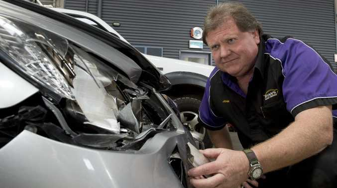 Ryan's Smash Repairs owner John Schriek inspects damage to a Honda sedan caused by a kangaroo or wallaby.