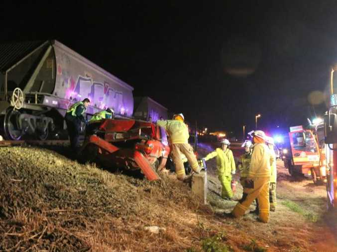 Emergency services work to free a driver trapped after being hit by a train in Gatton.