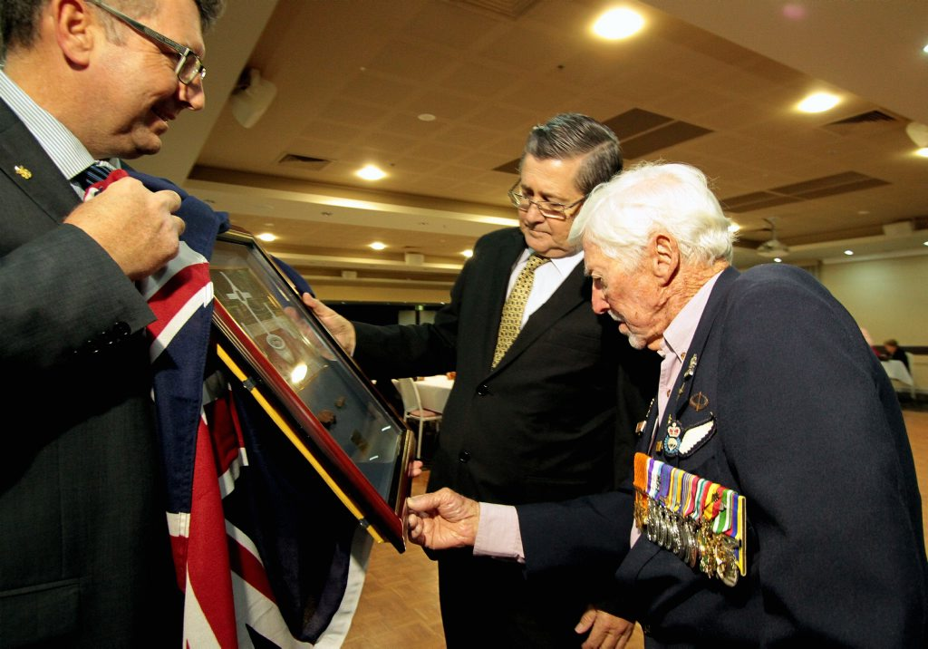 Vietnam veteran Harry Smith casts his eye over a framed photo and shrapnel held by federal member for Hinkler Keith Pitt and formally presented by Hervey Bay MP Ted Sorensen MP at the Hervey Bay RSL.