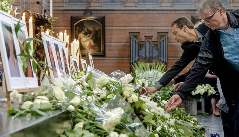 People place flowers under near photographs of victims during a memorial service in the Sint-Vitus church in Hilversum on August 17, 2014.
