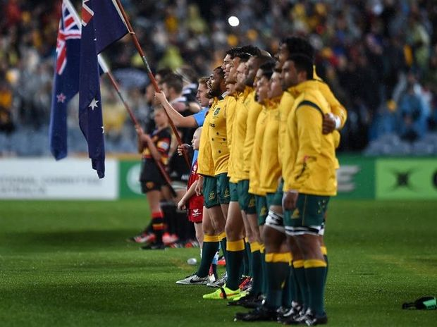 THANK YOU BALL BOY: Sam Carroll, in the Redmen shirt, sings the National Anthem with the Wallabies just before Saturday's Bledisloe Cup game. Photo: AAP Paul Miller.