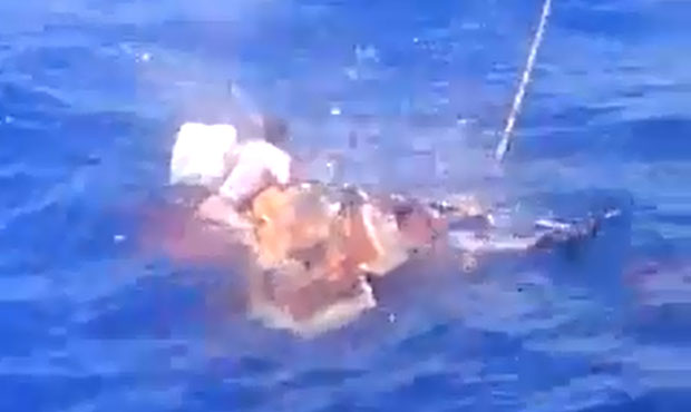 Three men are shown holding on to an upturned boat before being shot.