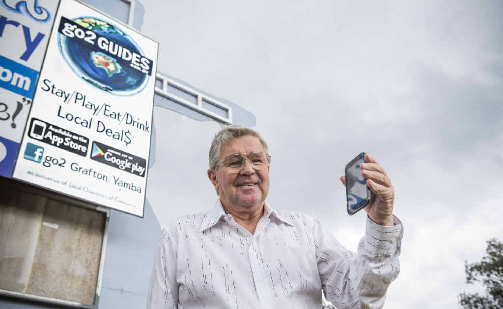 APPY MAN: President of the Maclean Chamber of Commerce John Riggall looks at the Go2Guide app in front of signage for it on the Pacific Hwy. Photo: Adam Hourigan