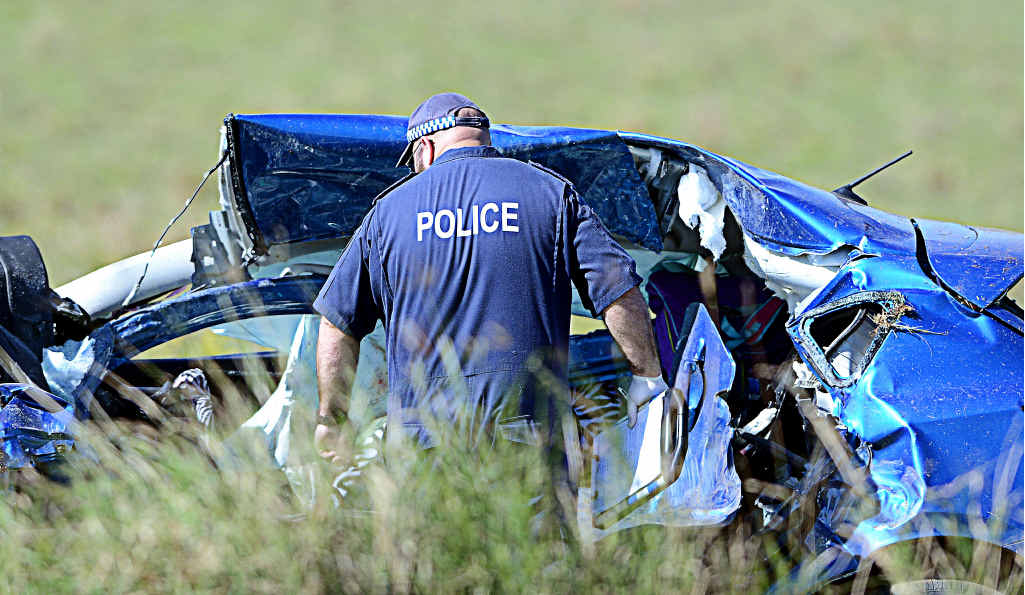 TRAGEDY: A crime scene investigation officer examines a car that was involved in the triple fatal crash at Dyraaba.