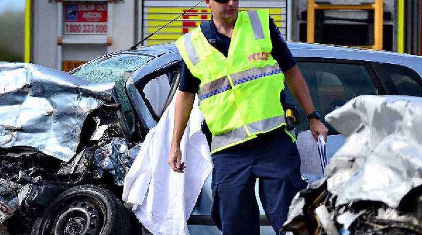 A police officer at the scene of a head-on crash on the Isis Hwy north of Childers where two Point Vernon fathers were killed.