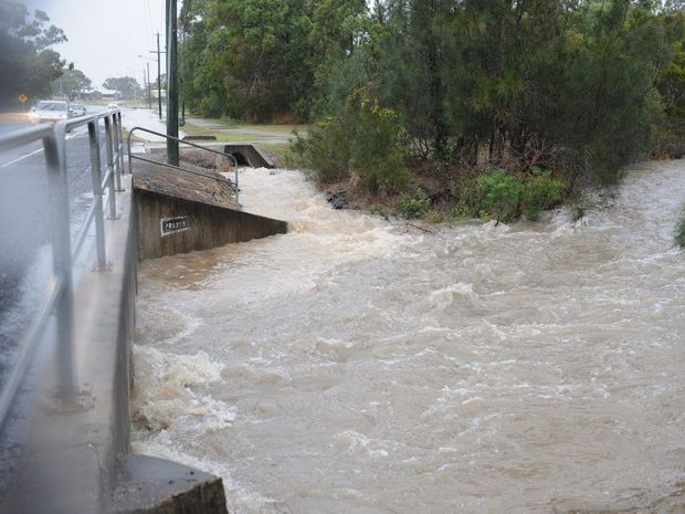 Rainwater gushes through one of the drains on Elizabeth St in Urangan on Saturday afternoon.