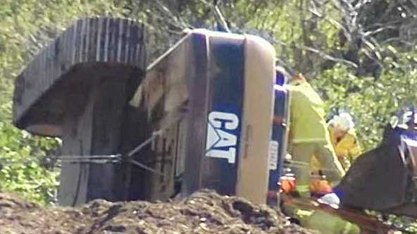 DUMPED: Firefighters work to free an excavator driver after his machine rolled over at the tip.