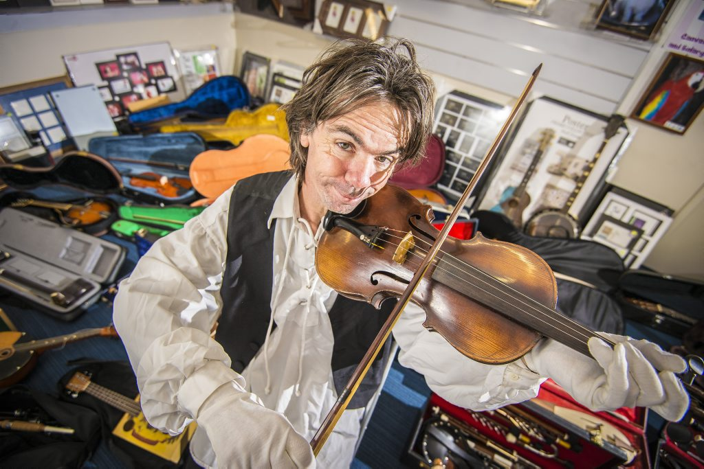 Ian Watts holds his 17th century violin, an Antonius Stradivarius Cremona Faciebat Anno 1681, amongst the rest of his collection.