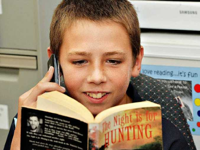 Nicholas Wallace of Mackay reading to a buddy on the phone. Photo Peter Holt / Daily Mercury