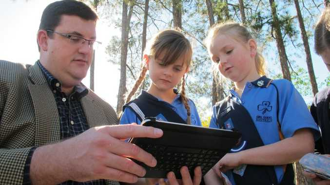Natural Resources Minister Andrew Cripps demonstrates the new QTopo program to Queensland Girl Guides Jo (left) and Jemma.