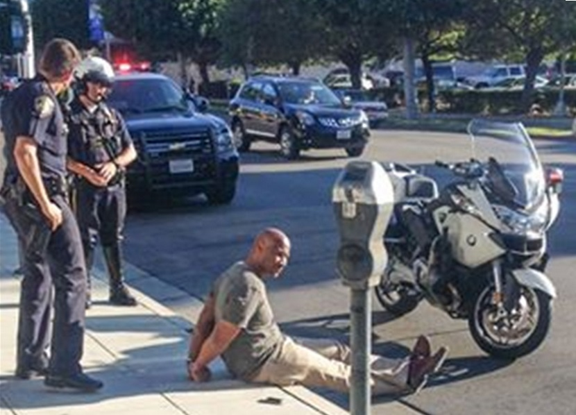 A photo of Charles Belk being detained by police on Friday 22 August