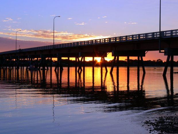 This photo taken at sunrise. It shows a different view of our Bribie Bridge with the sun rising between the pylons. I took this photo looking towards Bribie Island.