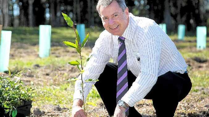 NEW START: Councillor Stephen Robinson plants a tree at the Doonan Creek Environmental Reserve.
