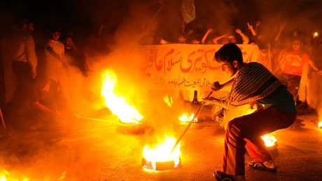 Pakistani activists of the hardline party Jamaat-i-Islami (JI) shout anti-US slogans and burn tires during a protest in Lahore early on September 24, 2010 following the sentencing of Pakistani scientist Aafia Siddiqui to 86 years in prison for trying to shoot US officers.