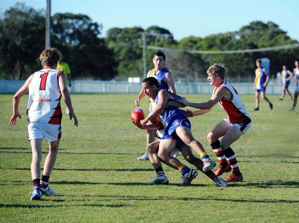 HOT POTATO: ATW midfielder Michael Blair gets the ball away in the preliminary final despite the attention of Jayden Grogan at Keith Dunne Oval in Hervey Bay. Photo: Griffith Thomas / Fraser Coast Chronicle