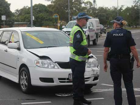 Police officers stand next to one of the cars involved in a crash on the corner of Robert St and Boat Harbour Dr in Urangan on Tuesday morning.