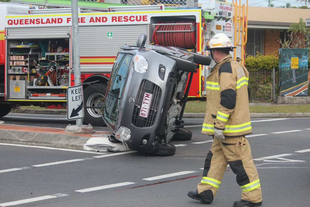 A firefighter walks around a car on its side after a crash on the corner of Robert St and Boat Harbour Dr in Urangan.