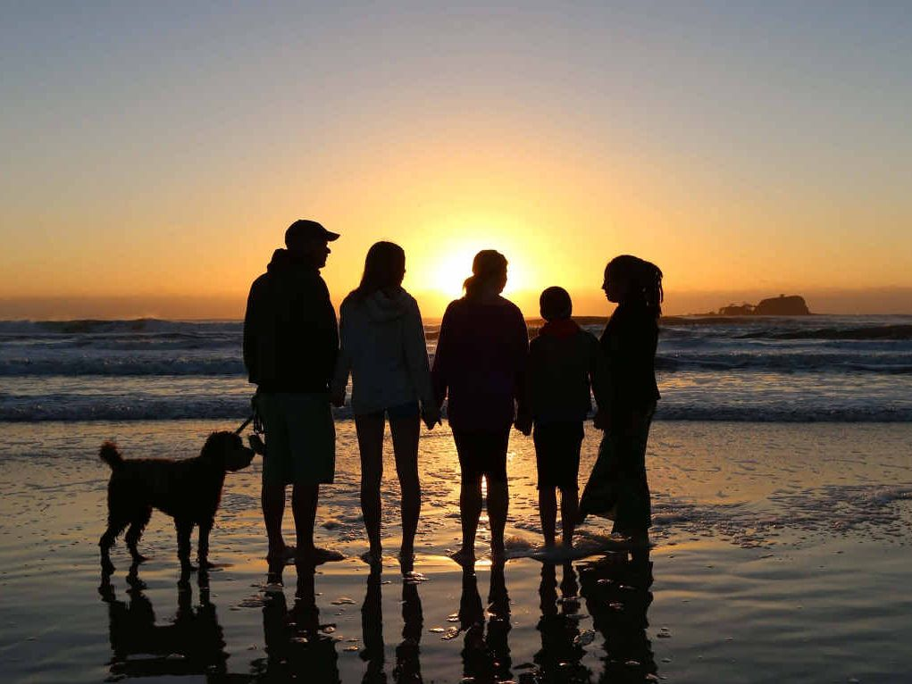 NEW DAWN: The Young family watch the sunrise over Old Woman Island at Mudjimba Beach.