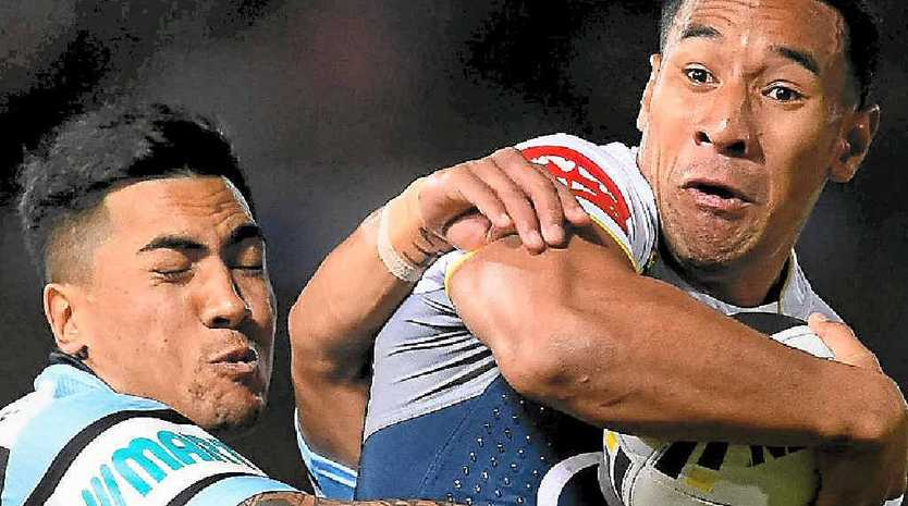 Tautau Moga of the Cowboys is tackled by Sosaia Feki and Ricky Leutele of the Sharks in Townsville last night.