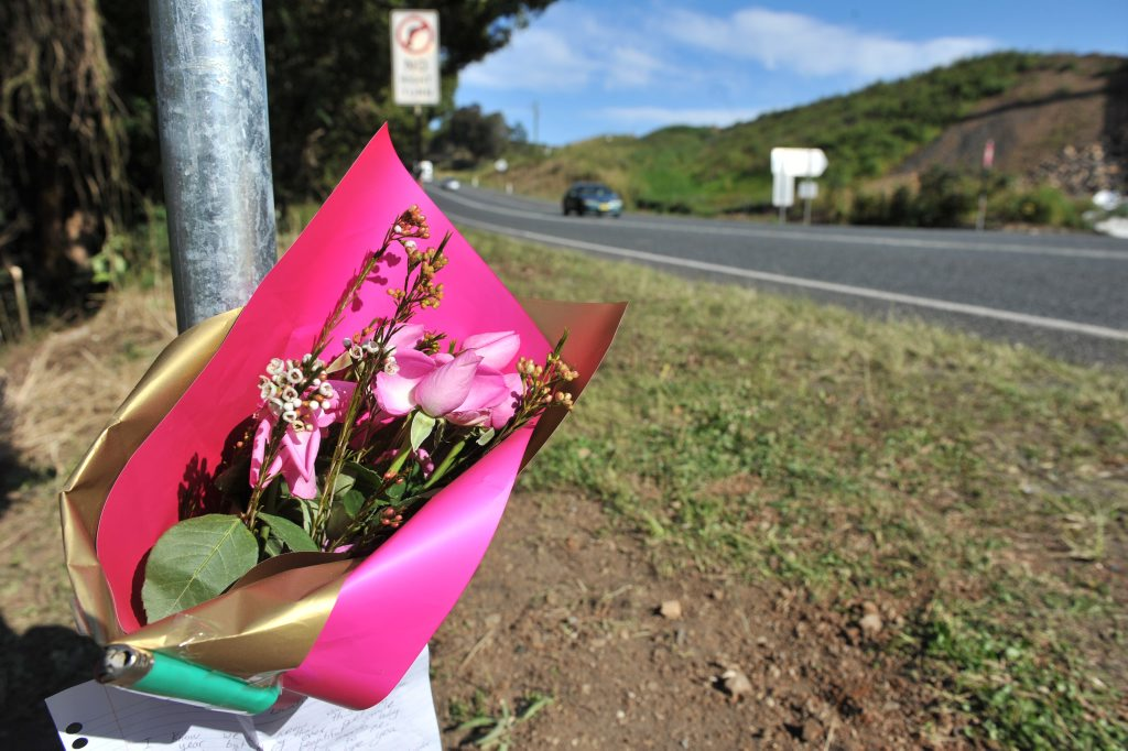 Flowers laid at the site of a single vehicle accident where four people were killed when the car left the road and collided with a tree near Newrybar.