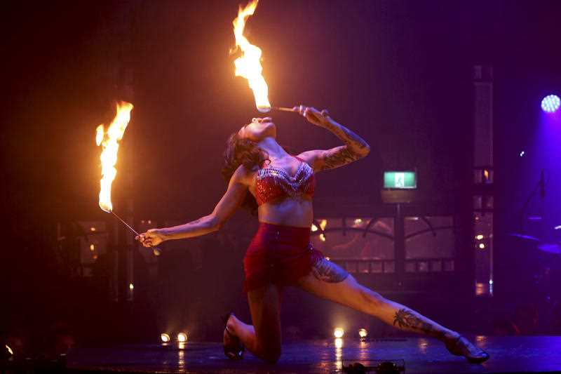 A woman breaths fire as she performs on stage during the Limbo circus-cabaret show during Sydney Festival in Sydney, Australia, Wednesday, Jan. 22, 2014. Limbo is an aerial acrobatics show filled with stunts and staggering illusions set to a thrilling live score of brass, electronics, hip-hop and club beats. S