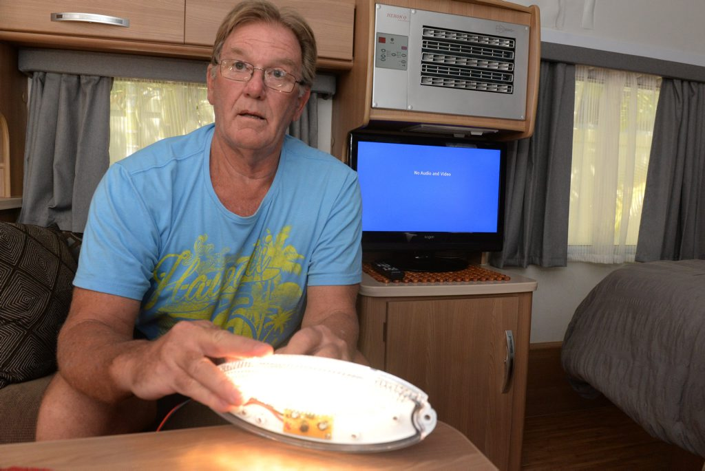 NO RECEPTION: Phil Shapcott demonstrates the effect his LED caravan lights have on his TV reception. Photo: Mike Knott / NewsMail