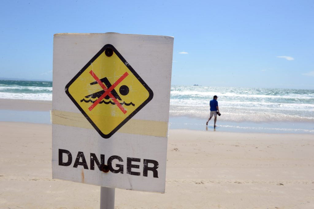 Warning signs remain in place on Clarkes Beach, Byron Bay the day after a fatal shark attack.