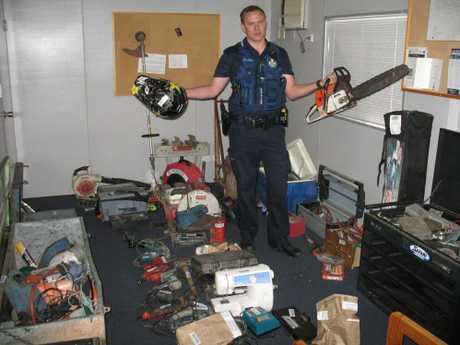 Goondiwindi police officer Constable Vaughan Clacher inspects stolen property recovered during raids as part of Operation Mike Bortec.