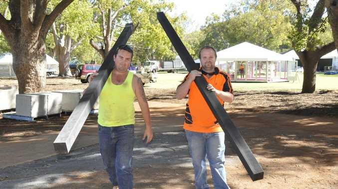 David Young and Drew Zegenhagen carry the posts to make a flower fence at Queens Park.