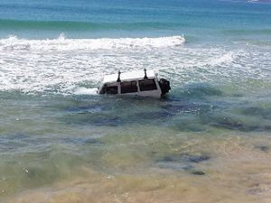 Man rescued before car swallowed by surf