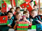 Hervey Bay Christian Academy student Kaden Vogler and classmates pack Christmas boxes for underprivileged children.