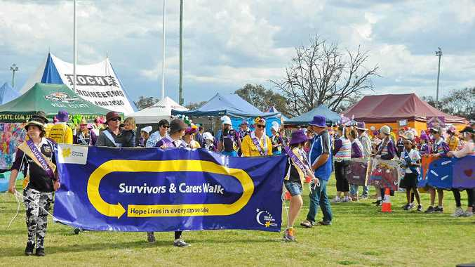TAKING PART: Sarah Worth (middle of banner) leads the opening lap of the 2014 Warwick Relay for Life.