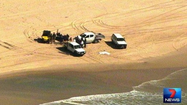 Police on the scene after a man's body washed up on South Stradbroke Island. Photo: Channel Seven/Twitter
