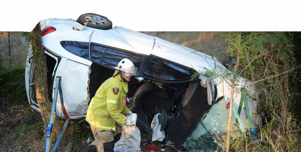 WRECK: A Gympie Fire and Rescue officer cleans up the wreckage of the crash on Gympie Wooloolga Rd near Widgee yesterday.