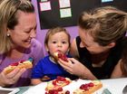 BERRY NICE: Cassandra Fenaughty (right) and Goodstart Early Learning Centre director Tash Sullivan tempt toddler Beauden May.