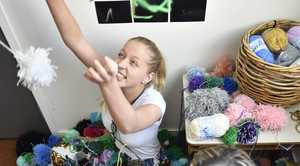 Artists at The Grid prepare work for Canival of Flowers exhibition. In amonst the pom poms they hae created for one of the works are Courtney Wagner (left) and Veronique Sirianni. Photo: Bev Lacey / The Chronicle