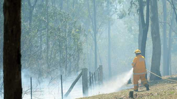 Firefighters work to put out a large bushfire along Leydens Hill Road before police ordered an evacuations after reports of gun shots fired at firefighters in the area. Photo: Chris Ison / The Morning Bulletin