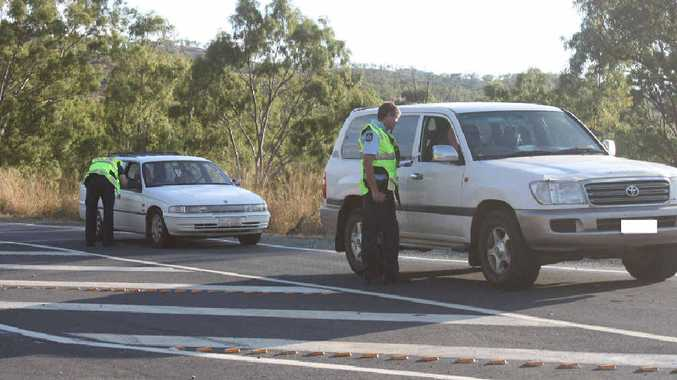 ROAD BLOCK: Police officers speak to motorists travelling down the Mt Morgan Range while a gunman was on the loose yesterday. Inset: Fire crews were called to fight bushfires.
