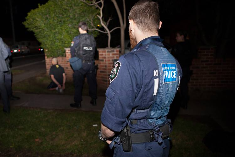 Officer watches on during the pre-dawn counter-terrorism raids