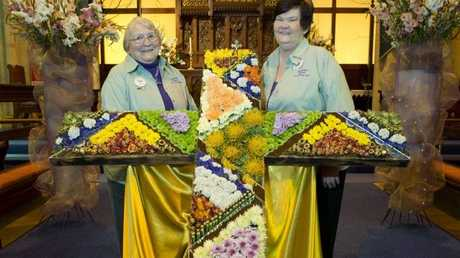 With the cross of flowers are Choral Chapman and Denise Harcourt at the St Luke's Anglican Church floral display for the Carnival of Flowers 2014.