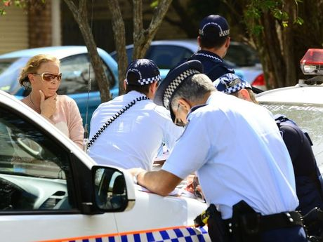 Emergency crews raced to the aid of a woman trapped beneath a car at a property in Redbank Plains. Police speak to neighbour Emily Downes (left) who helped at the scene. Photo: David Nielsen / The Queensland Times