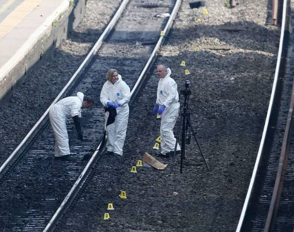 Forensic officers work on the tracks at Slough train station, west of London, after a woman and a child died after being struck by a train at the station