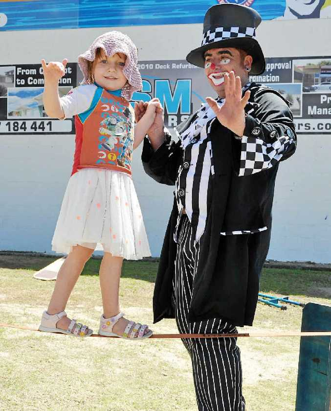 FINE LINE: Lilian Pointing walks the tight rope with Tyrone the Clown at the Beach Day Out for Disability Action Week.